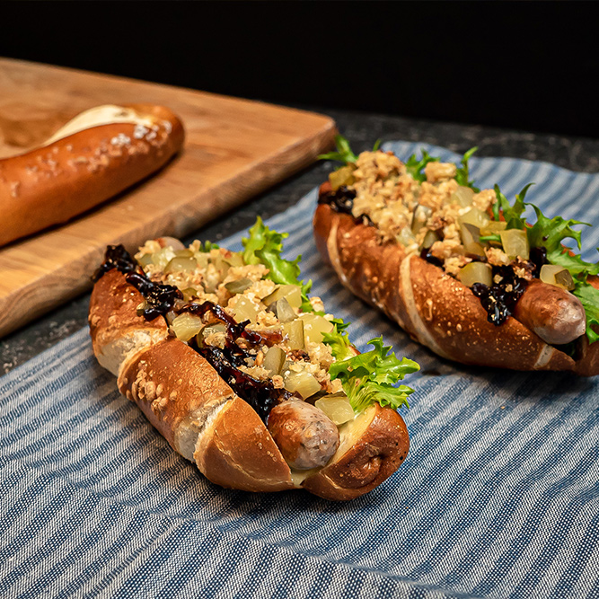 Pretzel hot dog with onion Jam and cauliflower & oat crumble